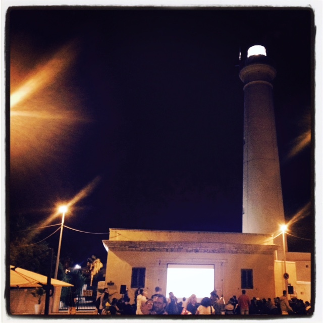 People attend Colin Pantall talk in the square under the famous lighthouse of Punta Secca