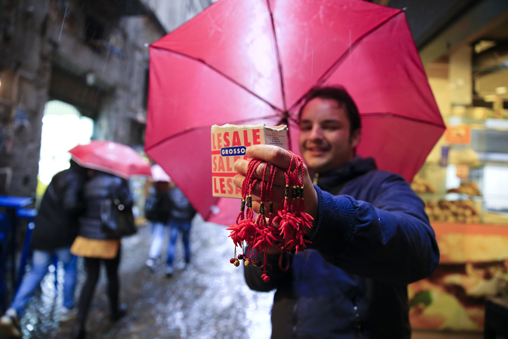 A man holds red horns and salt, that he uses to do a special good luck ritual for tourists, in downtown Naples, Italy February 14, 2018. REUTERS/Tony Gentile