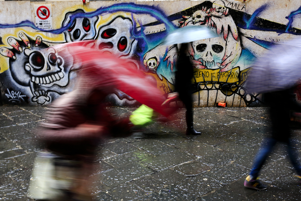 People walk past a murales depicting skulls in downtown Naples, Italy February 14, 2018. REUTERS/Tony Gentile